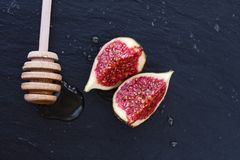 Two appetizing piece of fruit figs in honey and a wooden spoon on a black background. Two appetizing healthy sweet piece of fruit figs in honey and a wooden Stock Photography