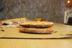 Two appetizing ruddy slices of pizza lie on top of each other. evaluation of quality, color and degree of baked crust. Stock Photography