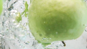 Two apple halfs fall down into water stock video