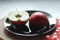 Two apple halves on a black plate stock photos