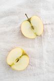 Two apple halves. On a linen tablecloth stock photo