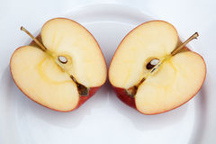 Two apple halves. Side by side on a white plate Stock Photography