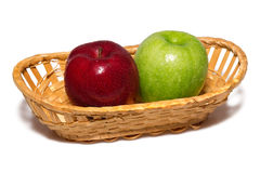 Two apples in a  basket. Two wet apples in a wattled basket on isolated Royalty Free Stock Photography