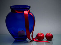 Two apples and blue glass vase with ribbon on gray Royalty Free Stock Photo
