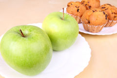 Two apples and cakes on white plates Royalty Free Stock Image