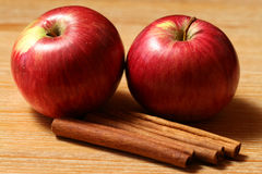 Two apples with cinnamon. Apples and cinnamon sticks - two juicy fruits on the wooden table Stock Image