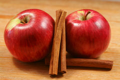 Two apples with cinnamon. Apples and cinnamon sticks - two juicy fruits on the wooden table Stock Photography