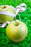 Two apples on grass and one with a tape measure Stock Photo