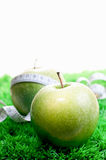 Two apples on grass and one with a tape measure Royalty Free Stock Photography