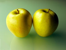 Two apples on green background. Two green yellowish Granny Smith apples on green glass background Stock Images