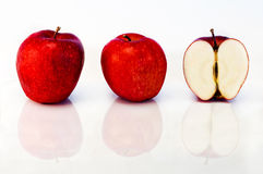 Two apples and a half. Two red apples and a half, mirror on white background Stock Images