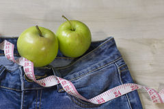 Two apples and jeans for weight loss. Two fresh green apples and blue jeans and measure tape for weight loss and good body form Stock Image