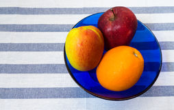 Two Apples and Orange in Blue Glass Bowl placed on Striped Backg Stock Photo