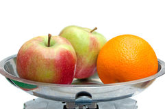 Two apples and orange on the libra Royalty Free Stock Image
