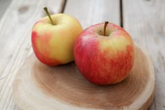 Two apples. On a small wooden shelf Stock Images