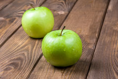 Two apples on a wooden background close up. Two green apples on a brown wooden background close up Royalty Free Stock Images
