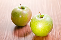 Two apples on wooden table Royalty Free Stock Photos