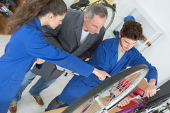 Two apprentices show manager how they repair bicycle Royalty Free Stock Photos