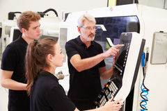 Two Apprentices Working With Engineer On CNC Machinery royalty free stock images