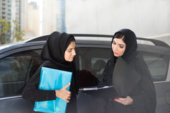 Two Arab Business Women Discuss Something. Two Arab Business Women with Folders Standing Next to a Car Are Discussing Something Royalty Free Stock Photos