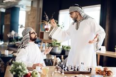Two arab businessmen arguing playing chess at table at hotel room. stock photo