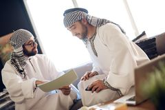 Two arab businessmen with papers at table at hotel room. stock photos