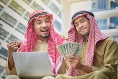 Two Arab businessmen rejoice in the success of their business ventures. Happy with the money received stock images