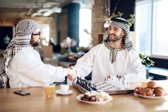 Two arab businessmen shake hands behind chessboard at hotel room. stock photo