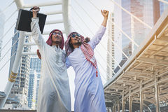 Two Arab businessmen standing by raising both hands. Up in city, Business good feeling concept royalty free stock photo