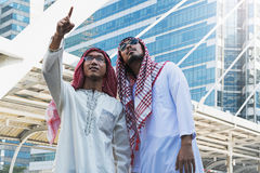 Two Arab businessmen standing by raising both hands up in city. Business good feeling concept royalty free stock images