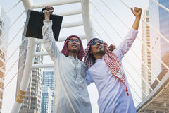 Two Arab businessmen standing by raising both hands up. In city, Business good feeling concept stock photo