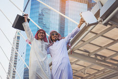 Two Arab businessmen standing by raising both hands up in city,. Business good feeling concept royalty free stock images