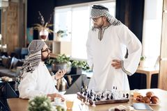 Two arab businessmen arguing playing chess at table at hotel room. royalty free stock images