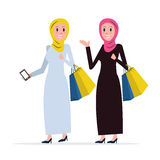 Two Arab women coming out of shopping with bags. Royalty Free Stock Photos