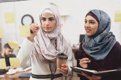 Two arab women working in office. Coworkers are taking notes on glass board. royalty free stock photography