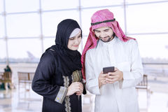 Two Arab workers use cellphone in airport Royalty Free Stock Image