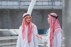 Two arabian businessman discuss, advise and walk together around. Modern city stock photo