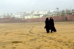 Two Arabic women are in a yashmak. CASABLANCA, MOROCCO 27 DECEMBER, 2013. Two Arabic women are in a yashmak go on the beach of the Atlantic ocean in Casablanca Stock Image