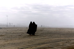 Two Arabic women are in a yashmak. CASABLANCA, MOROCCO 27 DECEMBER, 2013. Two Arabic women are in a yashmak go on the beach of the Atlantic ocean in Casablanca Stock Photography