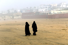Two Arabic women are in a yashmak. CASABLANCA, MOROCCO 27 DECEMBER, 2013. Two Arabic women are in a yashmak go on the beach of the Atlantic ocean in Casablanca Royalty Free Stock Image