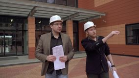 Two architect men are wearing construction helmets. Engineers are holding a building plan. SLOW MOTION. Architects inspecting construction site. a man and her stock footage