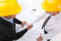 Two architect shaking hands over plan. Royalty Free Stock Image