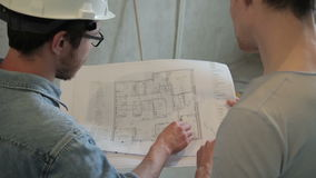Two architects analyze blueprint of building standing indoors. They hold construction documents in their hands and point with pen on details depicted on paper stock footage