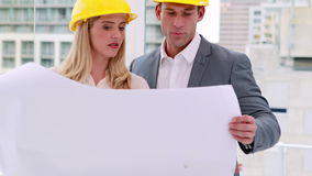 Two architects anaylzing plans together. In the office stock footage