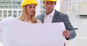 Two architects anaylzing plans together. In the office stock video