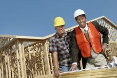 Two Architects With Blueprint At Construction Site Stock Photo