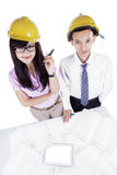 Two architects with blueprint looking at camera Stock Photo