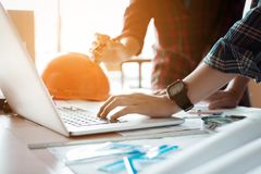 Two architects co-worker working together on project and using l royalty free stock photo