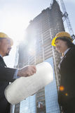 Two architects at a construction site holding blueprint Royalty Free Stock Images