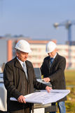 Two architects at construction site review plans Royalty Free Stock Photography